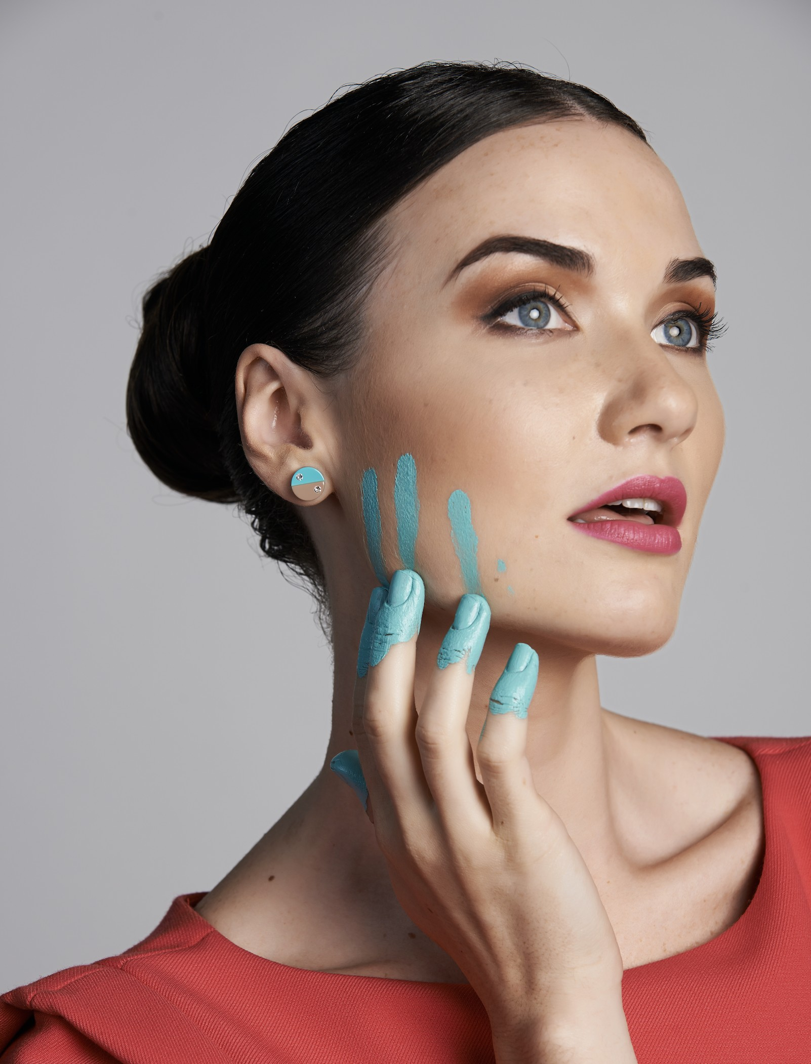 Kosmart model with Geometrix line earrings plays with colours on face